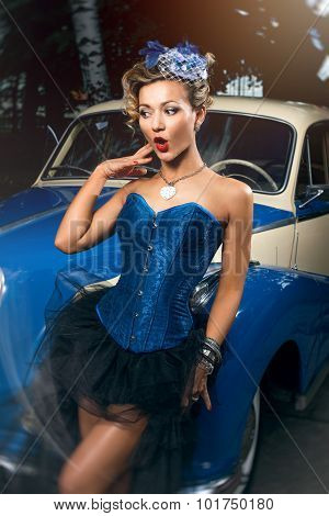 Beautiful woman in blue corset black skirt and elegant hat posing over retro car