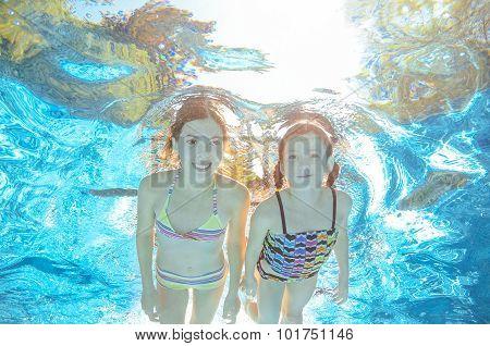 Children swim in pool or sea underwater, happy active girls have fun in water, kids sport