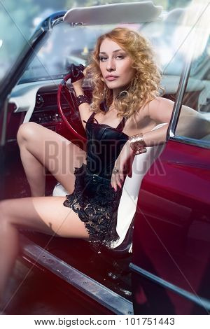 Woman posing over retro car in leather corset with lace skirt