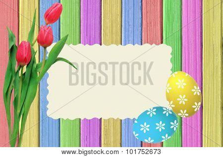 Colorful Easter Eggs, Pink Tulips And Postcard On Painted Color Wooden Texture