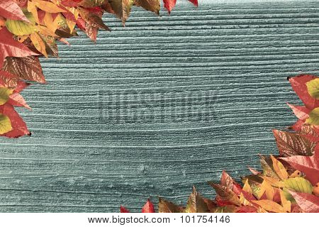Autumn leaves pattern against digitally generated grey wooden plank
