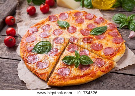 Sliced homemade Italian traditional pepperoni pizza with basil, salami, mozzarella cheese and tomato