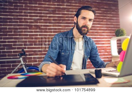 Portrait of businessman writing on graphic tablet while using laptop in creative office