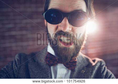 Portrait of angry fashionable man wearing sunglasses against brick wall