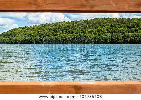 Beautiful lake in the summer landscape. View through a wooden frame from pier. Vacation and holiday