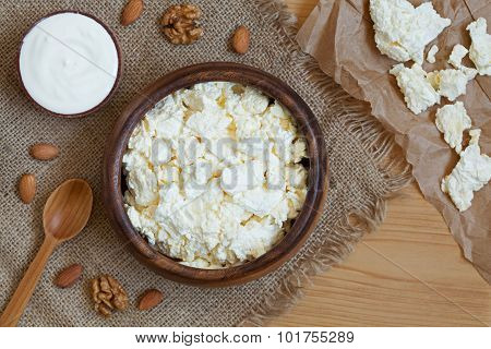 Homemade cottage cheese healthy dairy product with nuts in rustic wooden dish on vintage kitchen tab