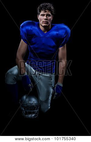 Portrait of confident American football player holding helmet while hand on knee against black background