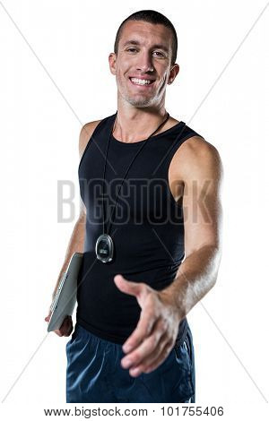 Portrait of welcoming personal trainer giving handshake against white background