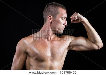Serious shirtless athlete flexing muscles against black background