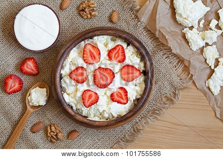 Cottage cheese healthy breakfast food with sour cream, fresh strawberry and nuts in rustic wooden di