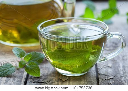 Fresh natural green melissa herbal tea in glass cup. Organic aromatherapy relaxation medical healthy