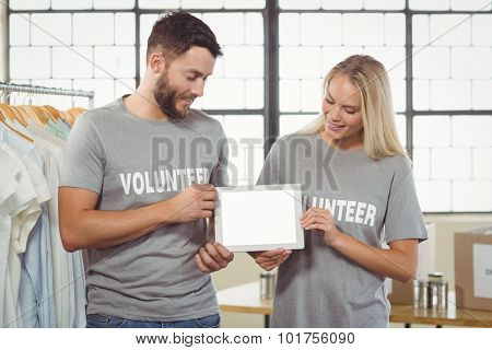 Colleagues holding digital tablet in creative office
