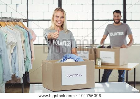 Portrait of smiling volunteer gesturing thumbs up with man in backkground
