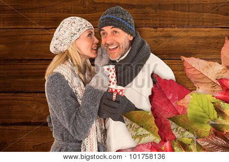 Happy couple gossiping while drinking hot tea against overhead of wooden planks