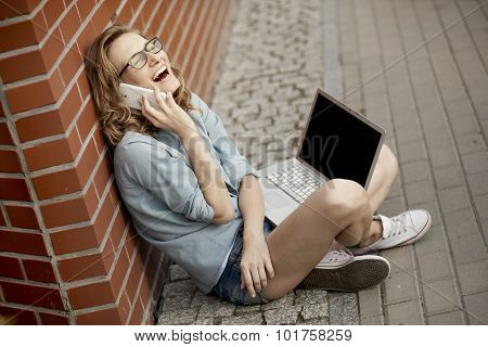 Young student having good time using phone while working outside with laptop