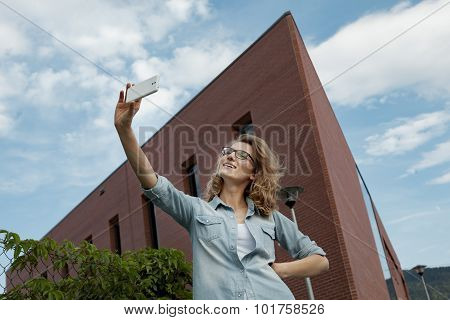 Happy young blonde caucasian woman taking a selfie portrait with mobile phone at the modern brick wa