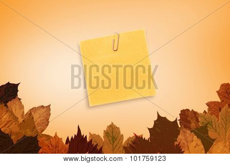 Orange adhesive note with a paperclip against autumn leaves pattern