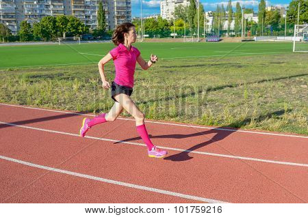 Happy active woman running on track, sprinting and working out on stadium, sport and fitness in city