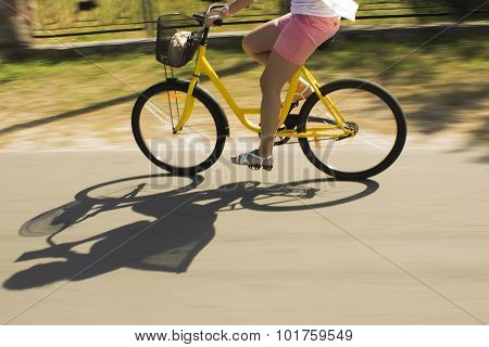 Motion blur.Riding yellow bicycle on the forest road. Close-up of young woman riding bicycle