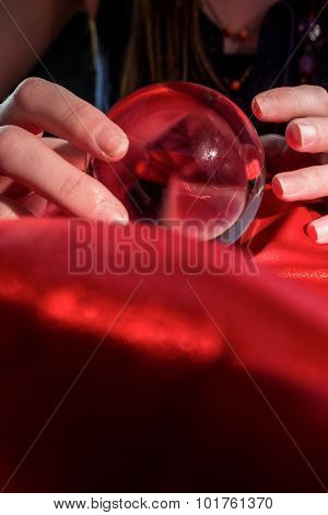 Fortune teller using crystal ball on red silk