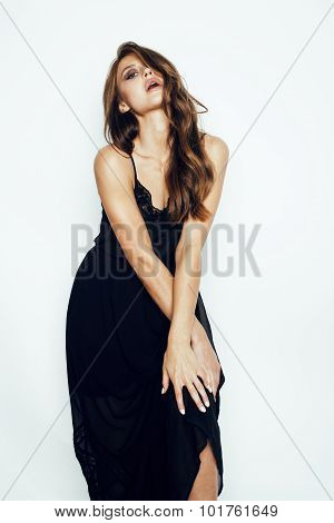 young brunette pretty woman in black dress posing on white background with make up