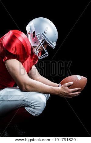 American football player crouching while holding ball against black background