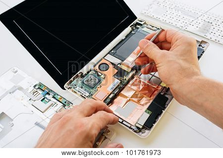 The Engineer Repairs The Laptop (pc, Computer) And The Motherboard