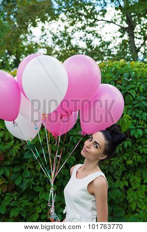 young woman with balloons on a background of green hedgerow