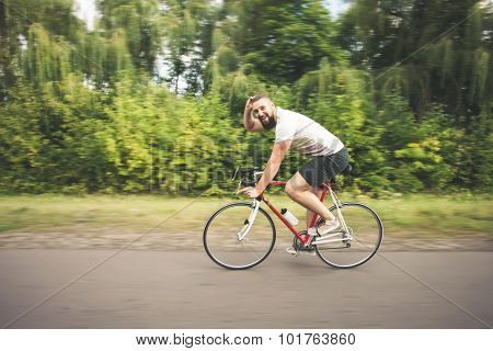Young Hipster Man Driving Fast Bicycle