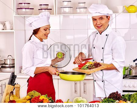 Happy man and woman professional in chef hat cooking chicken.