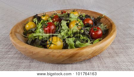 Fresh lettuce and red and yellow cherry tomatoes on a wooden tray.