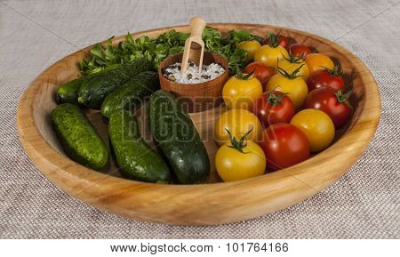 Fresh red and yellow cherry tomatoes and cucumbers with salt shaker on wooden tray in a rustic style. Good ingredients for the salad, cucumbers, tomatoes and green salad mix.