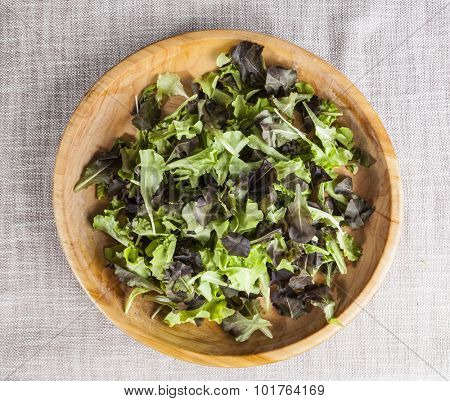 Fresh green salad lettuce on a wooden tray.