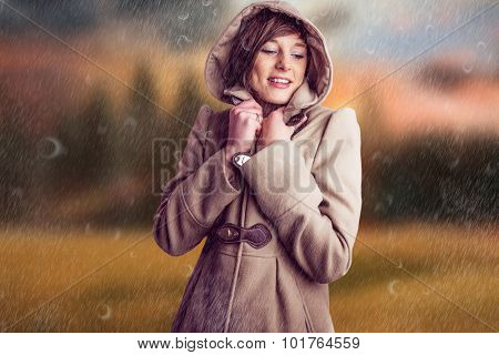 Smiling woman in winter coat against country scene