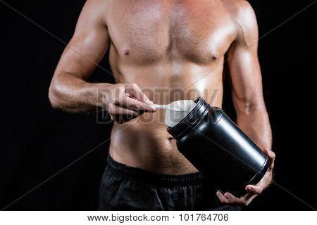 Midsection of shirtless man scooping up protein powder on black background