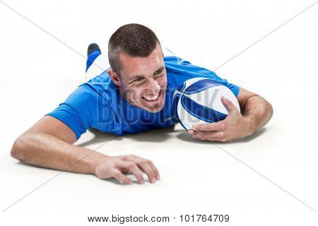 Confident rugby player lying in front with ball against white background