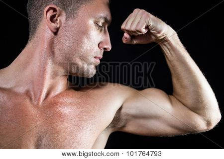 Close-up handsome shirtless athlete flexing muscles against black background