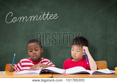 The word committee and cute pupils writing at desk in classroom against green chalkboard
