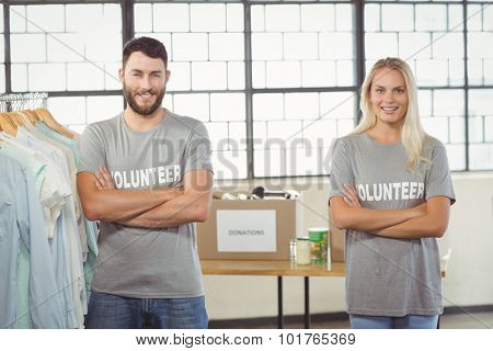 Portrait of happy man and woman with arms crossed standing by clothes rack in office