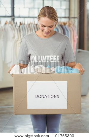 Happy volunteer holding clothes donation box