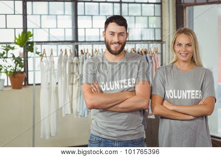 Portrait of smiling volunteers with arms crossed standing in office