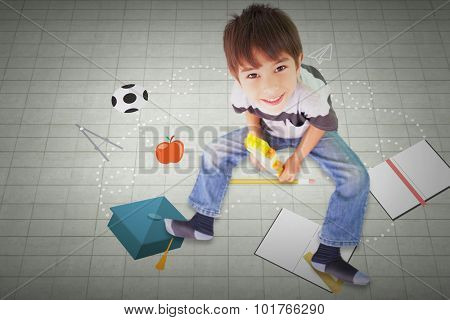 Cute boy sitting with building blocks against textured background