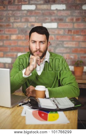 Portrait of serious businessman with hand on chin sitting in office