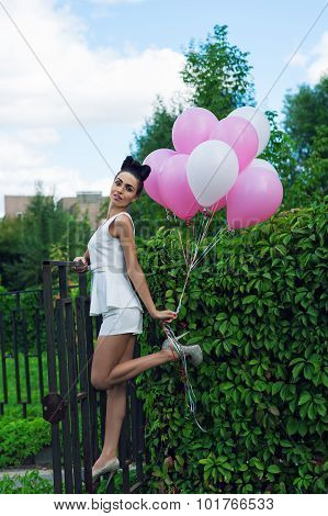 attractive woman with balloons in the street
