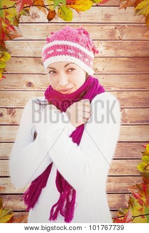 Attractive woman wearing warm clothes against autumn leaves on wood