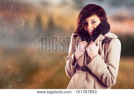 Portrait of beautiful woman in winter coat against country scene