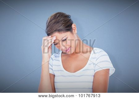 Beautiful woman suffering from headache against blue background
