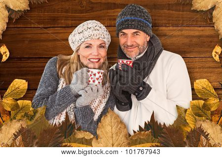Portrait of couple drinking hot coffee against overhead of wooden planks