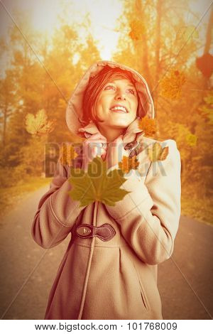 Smiling beautiful woman in winter coat looking up against autumn scene
