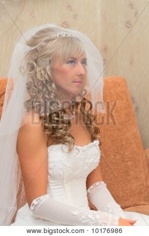 Bride Of A Beautiful Young Blonde Girl Is Sitting On The Couch With A Veil On Her Face. White Dress,